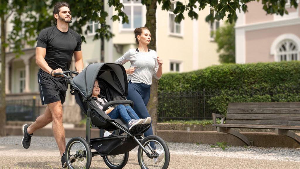 Mann und Frau joggen mit Kinderwagen durch einen Park