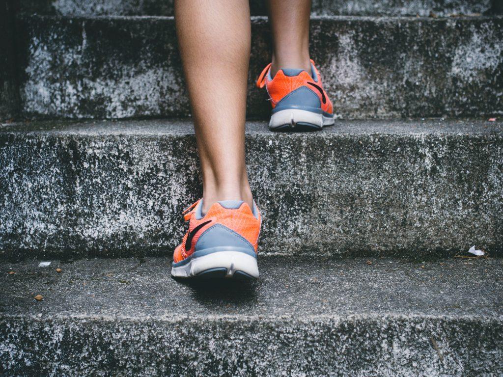 Frau mit Joggingschuhen steigt Treppe