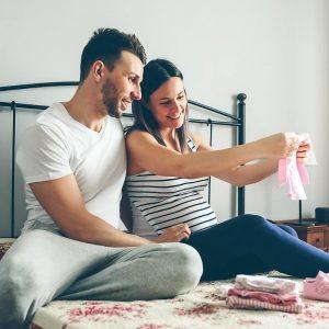 Schwangere Frau und Partner sitzen auf einem Bett und betrachten Babykleidung