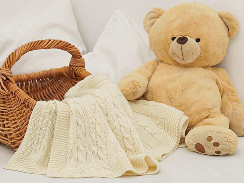 Korb mit gestrickter Decke und Teddybär