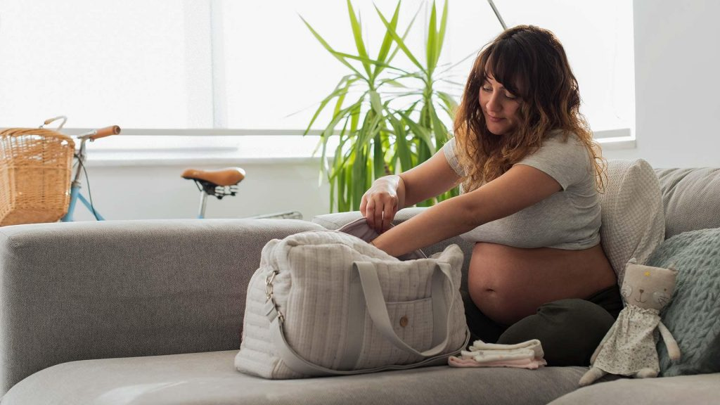 Schwangere packt ihre Kliniktasche auf dem Sofa