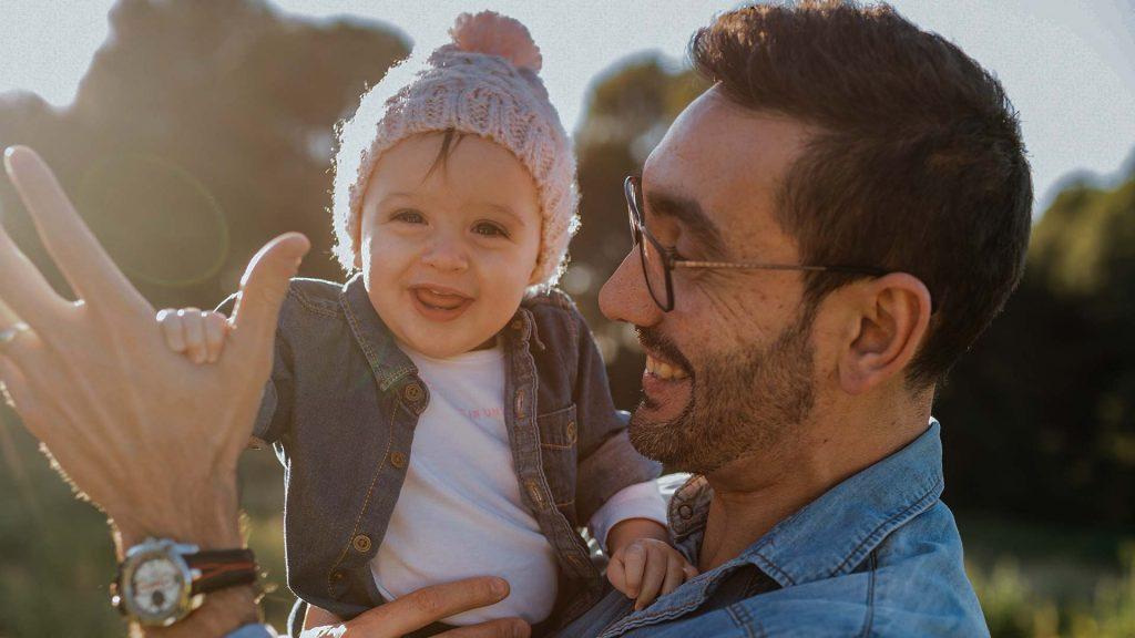 Vater mit Kind auf dem Arm im Grünen
