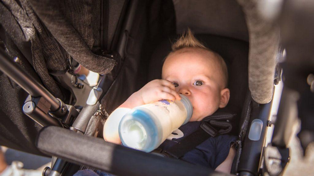 Baby sitzt im Kinderwagen und trinkt Milch aus einer Flasche