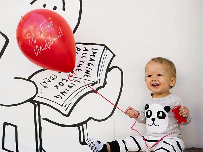 Kleinkind mit einem roten Ballon, der die Ankunft eines Geschwisterchen verkündet