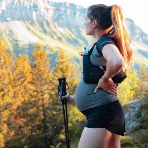 Schwangere Frau mit Wanderstöcken betrachtet Aussicht beim Wandern in den Bergen