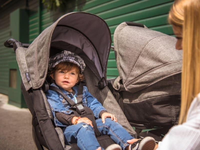 Kleinkind sitzt im Kinderwagen und Frau kniet davor