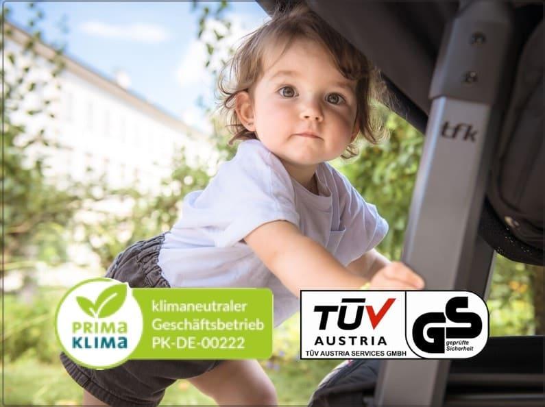 Kleinkind stützt sich auf das Gestell eines Kinderwagens um aufzustehen