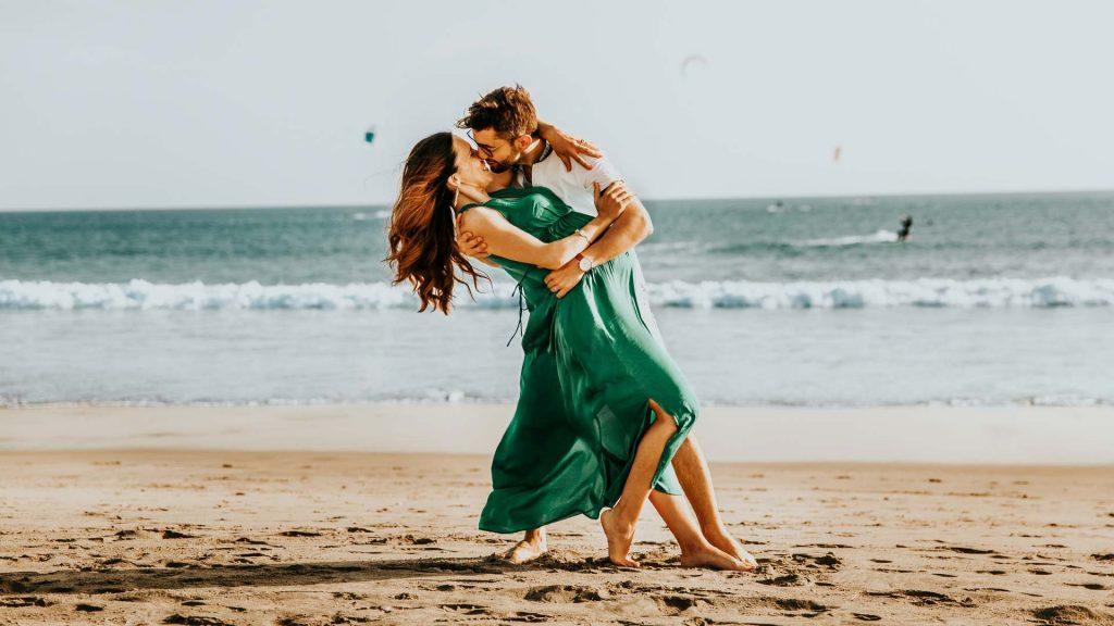 Schwangeres Paar in enger Umarmung am Strand.