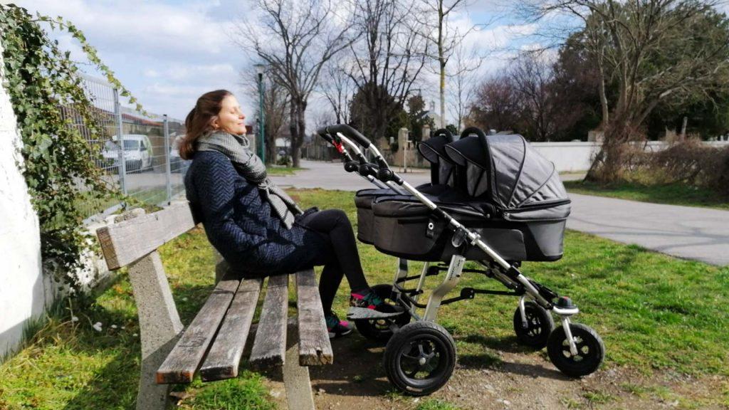 Frau entspannt beim Spaziergang mit Kinderwagen auf einer Bank