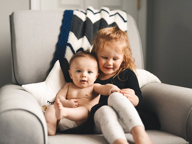Geschwister sitzen zusammen auf einem Sessel.