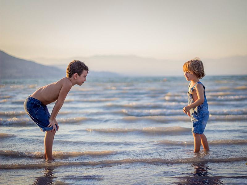 Geschwister spielen am Meer.