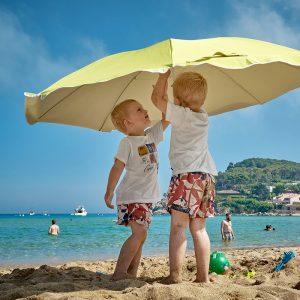 Zwei Geschwister stehen unter einem Sonnenschirm am Strand