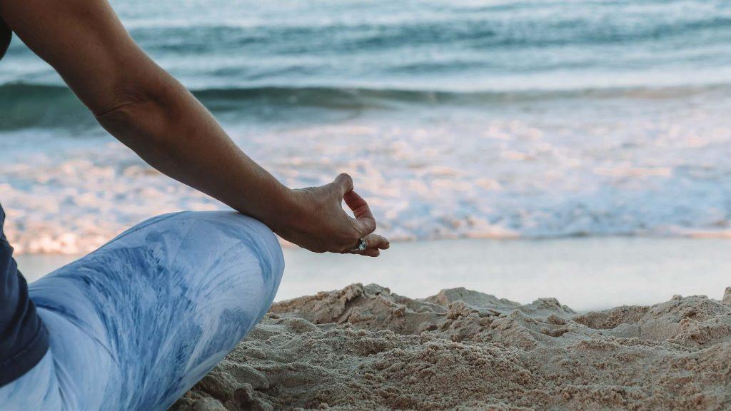 Schwangere Frau meditiert und macht Yoga am Strand